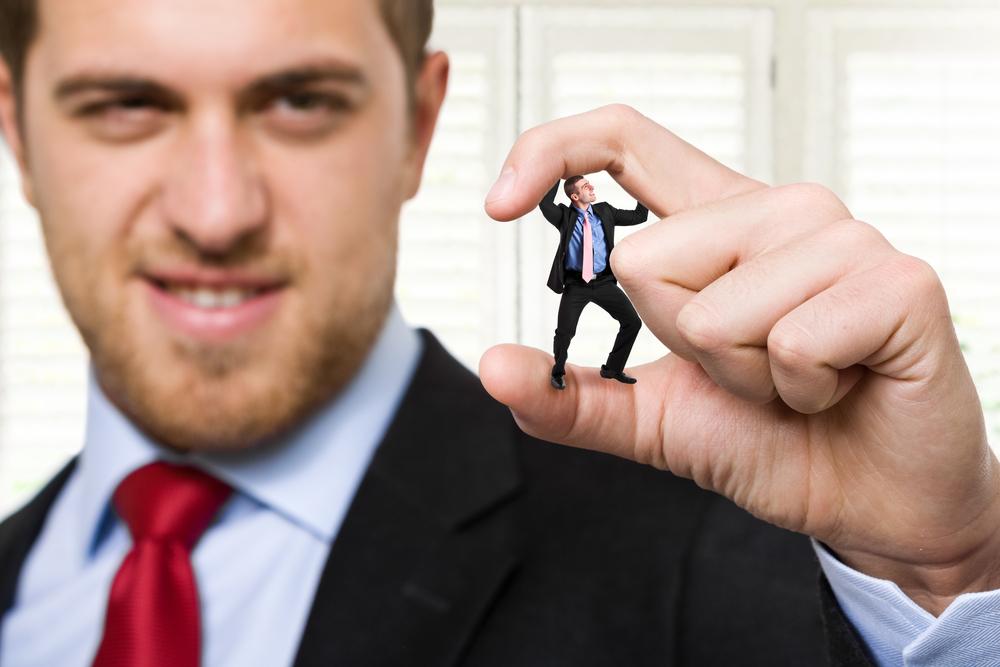 man crushing tiny teammate between his fingertips