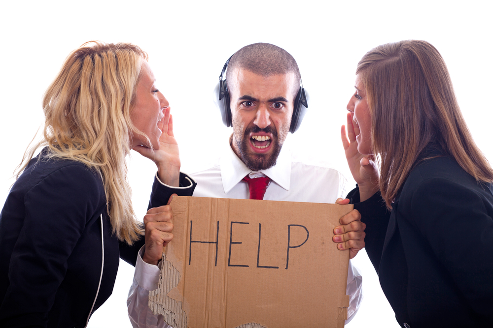 person wearing headphones and holding up sign saying 'help' while two colleagues yell