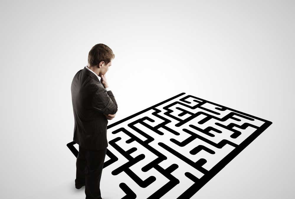 person standing contemplating a maze on the floor