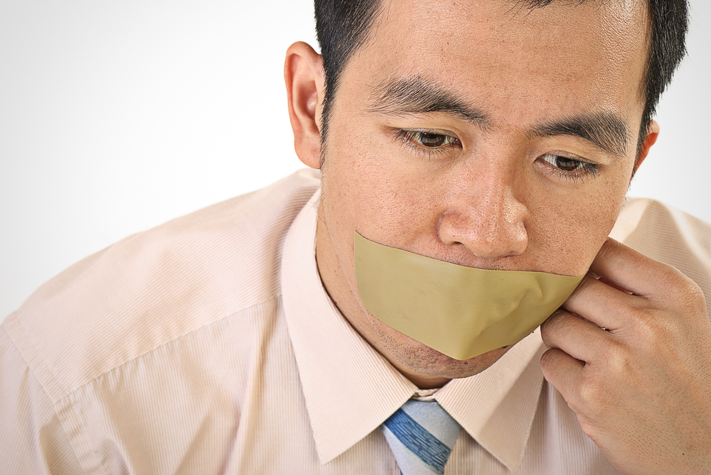business person with tape covering their mouth
