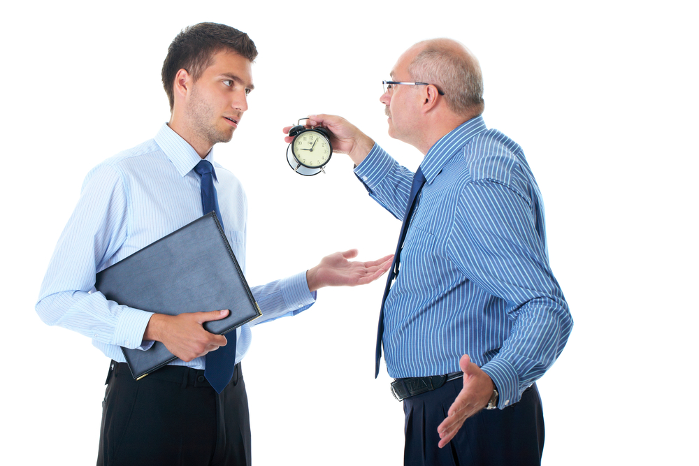 boss holding up clock and reprimanding employee