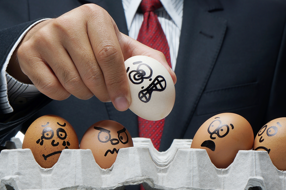 boss holding up eggs painted with scared expressions
