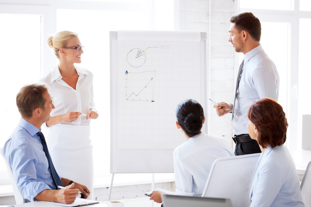 group of people standing around a flipchart