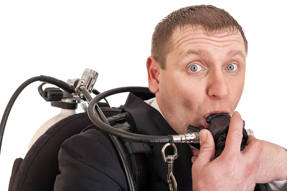 business person breathing through an oxygen tank