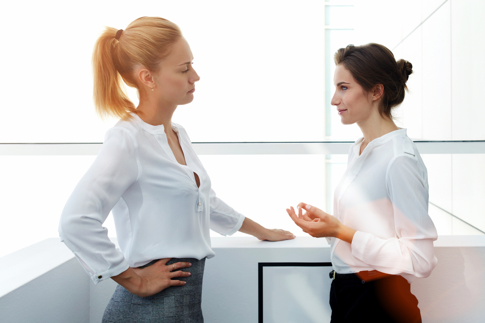 Two people standing face to face talking