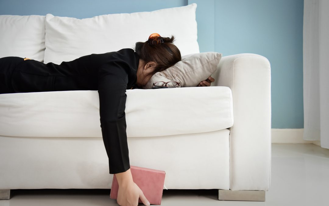Business woman collapse face-down on couch